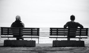 two people waiting on benches by the sea